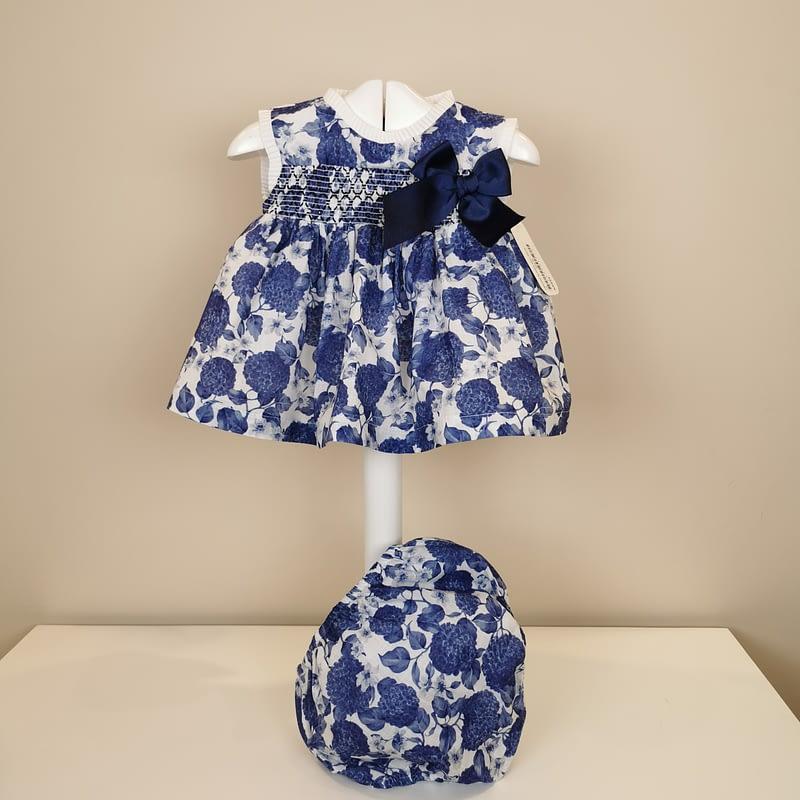 Vestidito con un precioso estampado en azul,tirante ancho,pechera en nido de abeja,cuello y mangas con plisado blanco, lazo marino lateral.