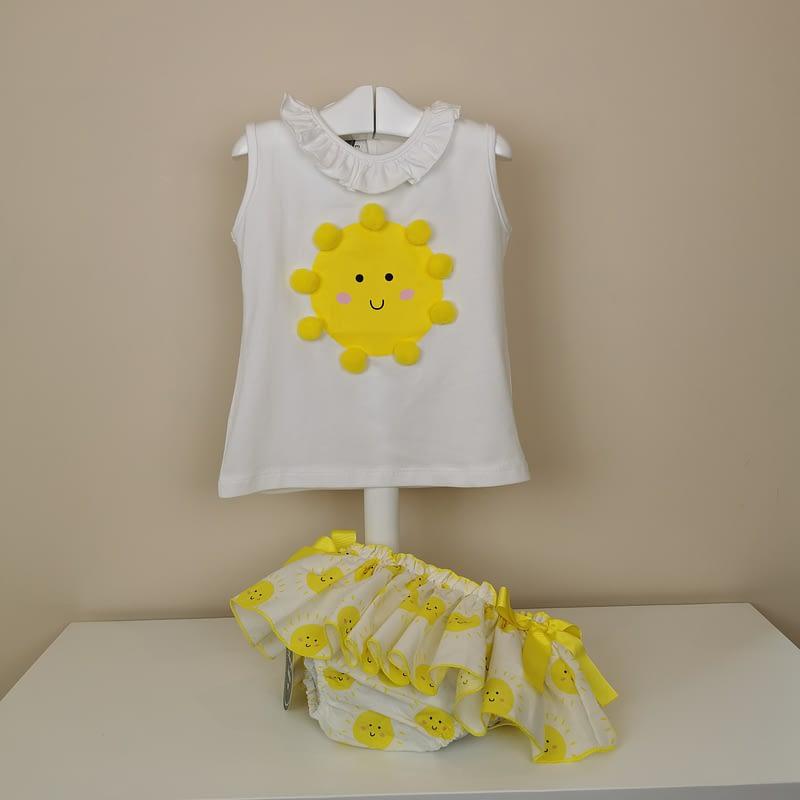 Camiseta manga sisa,volantito en cuello, sol impreso con detalle de pompones. Braguita con estampado de soles,volante ribeteado en amarillo con lazos laterales.