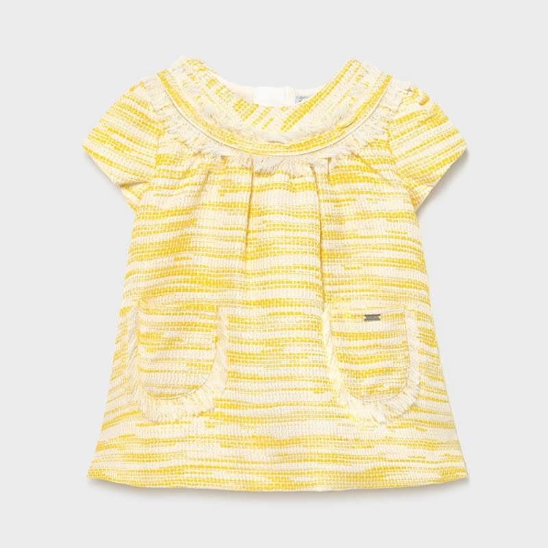 Tejido tipo chanel en amarillo y blanco roto. Corte evasé, para mayor comodidad, bolsillos plastrón, ribeteado de fleco cortito en cuello y bolsillos. Cierre cremallera en espalda. Manga corta.