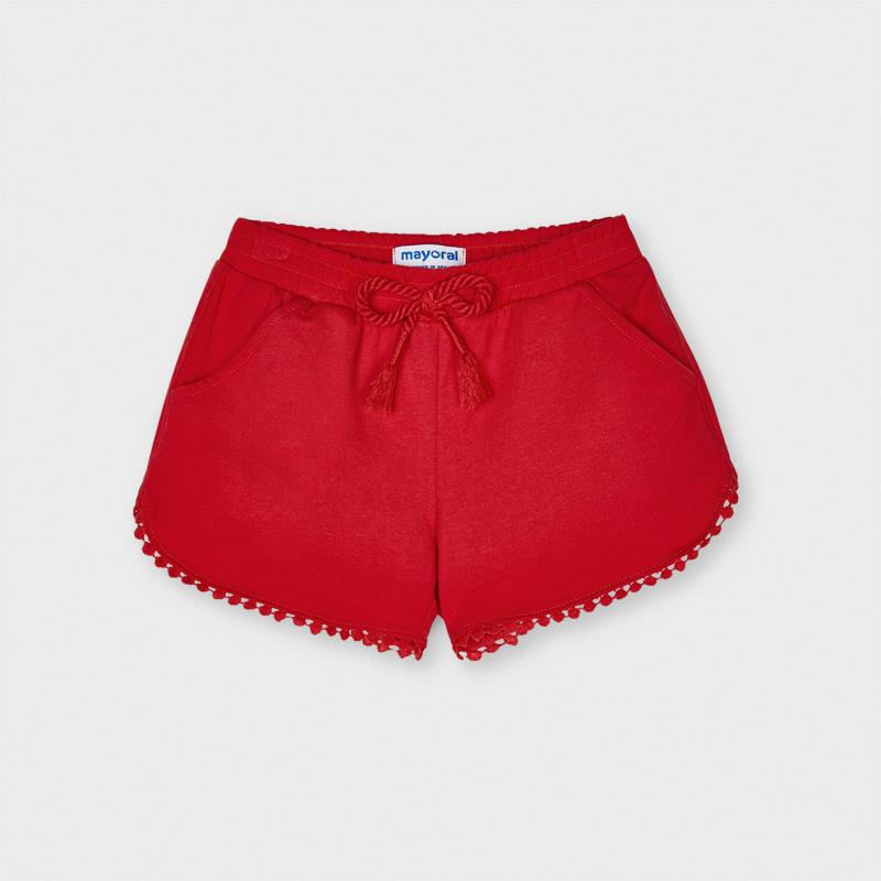 Pantalón corto de tipo short para niña. Cintura elástica con cordón ajustable. Cómodo tejido de punto. Diseño con detalles en el bajo al tono. Pequeñas borlas de adorno. Consultanos disponible en varios colores.
