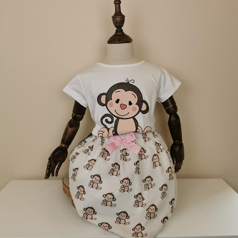Conjunto super dulce, compuesto de camiseta blanca con monito en marrón con glitter. Falda con estampado de monitos,goma cintura y lazo rosa.